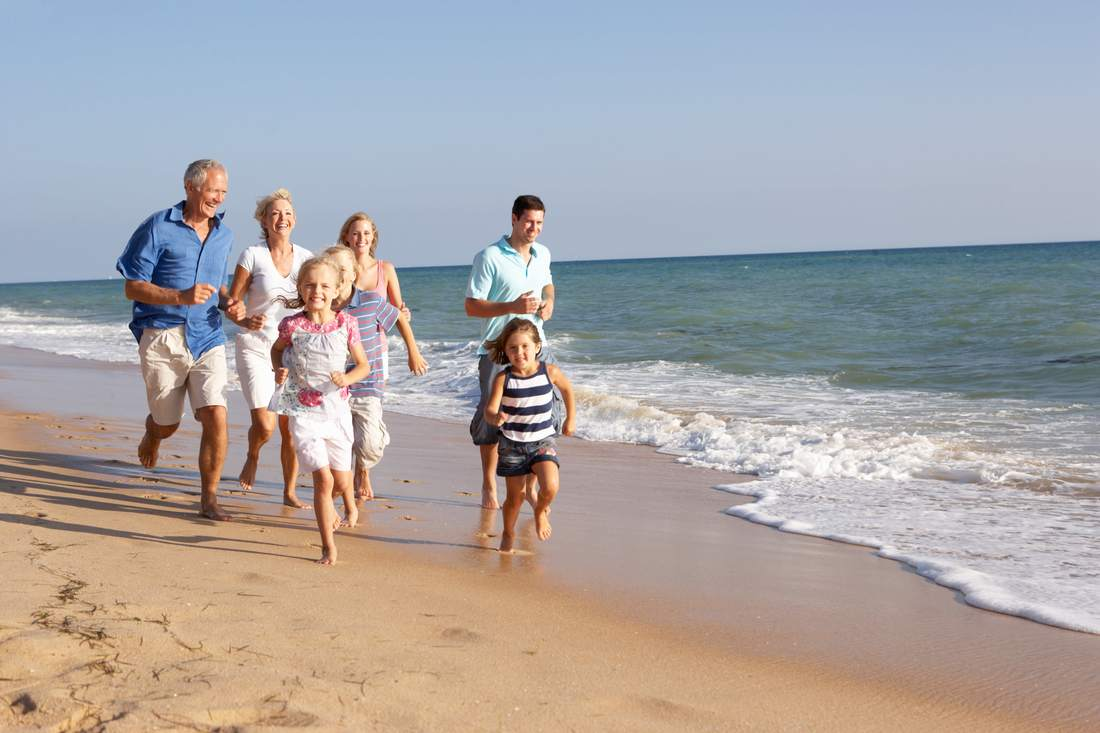 Multigenerational family running on beach